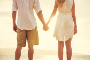 Young couple in love, Attractive man and woman enjoying romantic evening on the beach, Holding hands watching the sunset